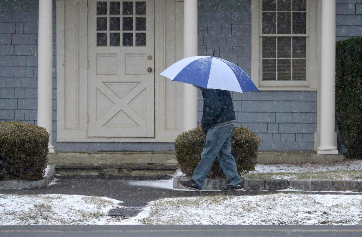 A pedestrian walks in the snow covered by a large umbrella Tuesday afternoon in Danbury, Conn. January 26, 2021.