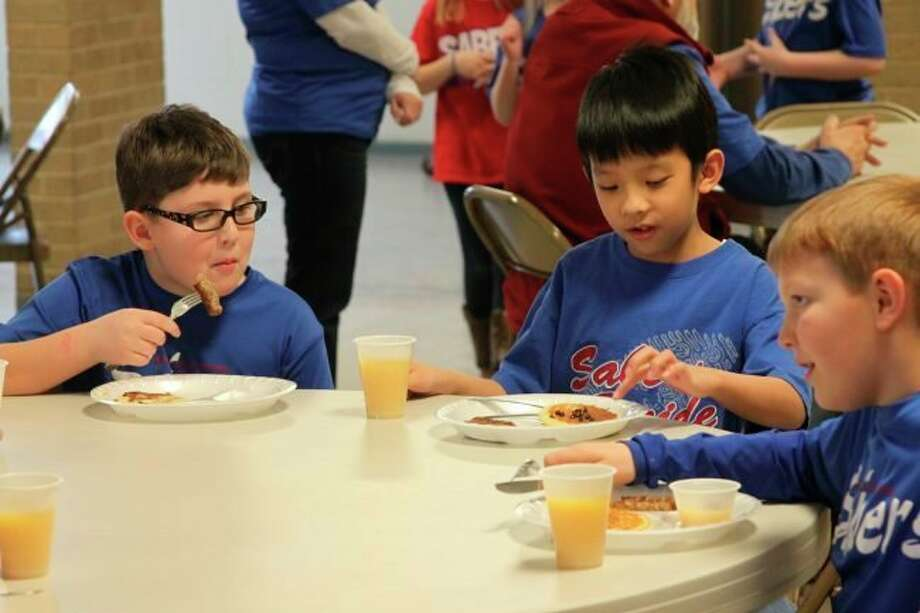 These three Manistee Catholic Central Elementary School students enjoy the pancake lunch that was prepared for the entire school by the Divine Mercy Men's Club as part of Catholic Schools week in 2018, an annual tradition. (File photo)