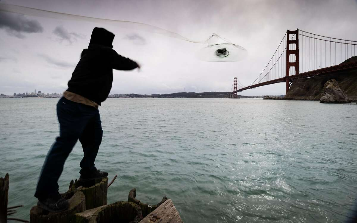 A fisherman throws out a crab net below the Golden Gate Bridge in Sausalito, Calif. on January 26th, 2021