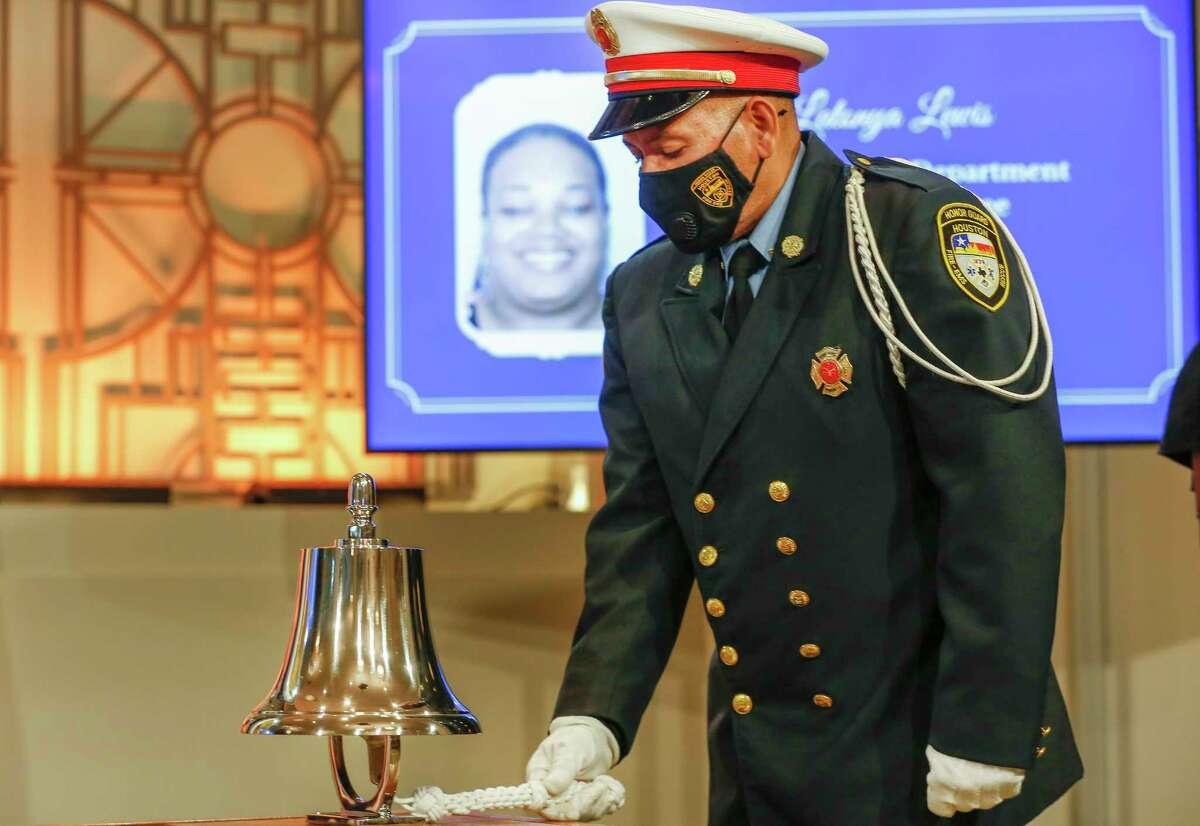 Houston Fire Department Honor Guard Assistant Commander Carlos Pascualli rings a bell as Mayor Sylvester Turner led a local memorial to lives lost to COVID-19 Tuesday, Jan. 19, 2021, in Houston. Participants honored all lives lost in Houston, Harris County and the state of Texas to COVID-19 complications.