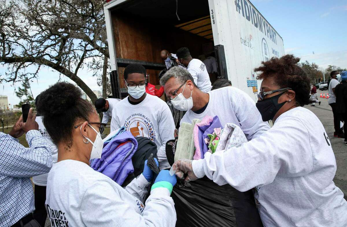 Veronica Smith, from front left, her nephew Nicholas Rogers, 17, her brother Herman Rogers, and her sister Catherine Rogers help load donated items Monday, Jan. 18, 2021, at MacGregor Park in Houston. The event was part of the MLK Day Virtual Experience and Parade of Giving.