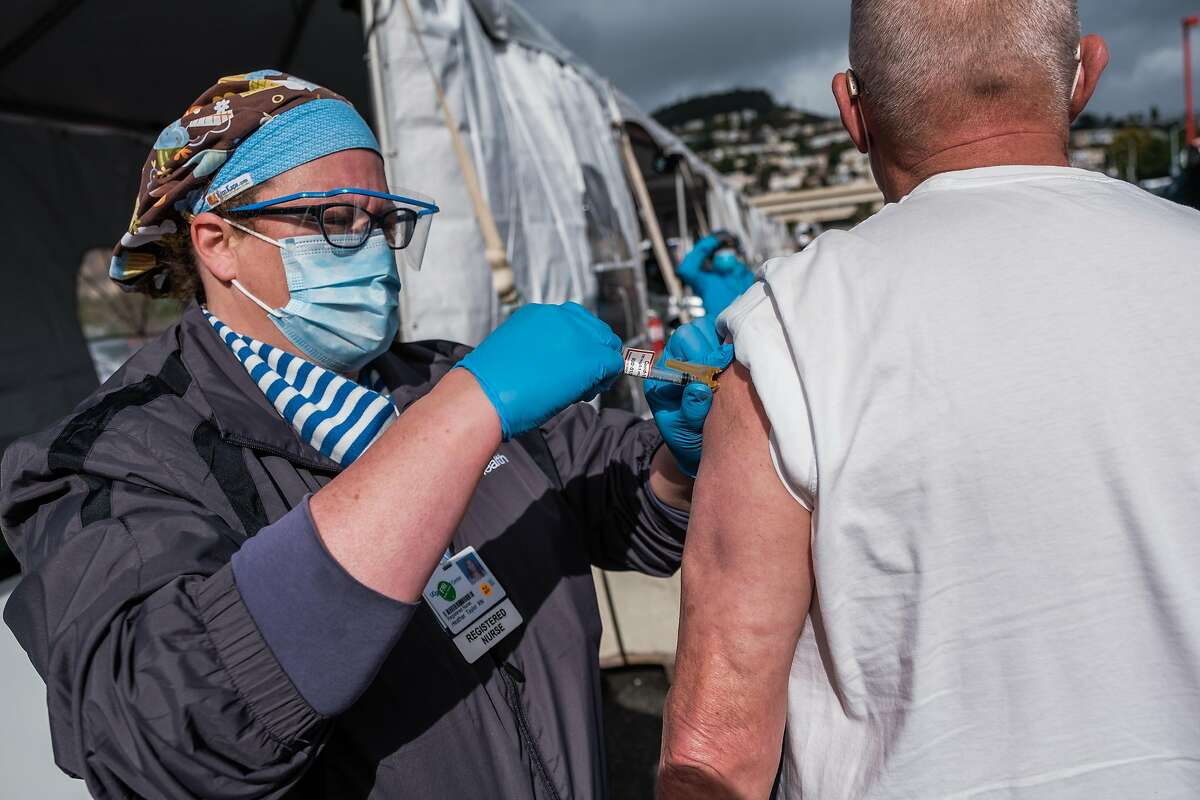 Heather Taylor administers a shot Friday at the mass vaccination center at City College.