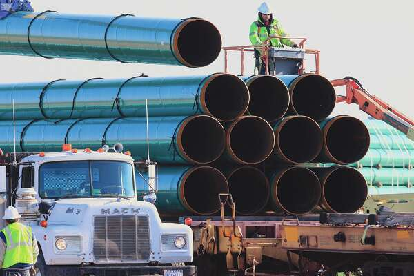 Workers unload pipes during construction of the Dakota Access oil pipeline that stretches from the Bakken oil fields in North Dakota through west-central Illinois. A federal appeals court Tuesday upheld the ruling of a district judge who ordered a full environmental impact review of the pipeline over a complaint by the Standing Rock Sioux Tribe.