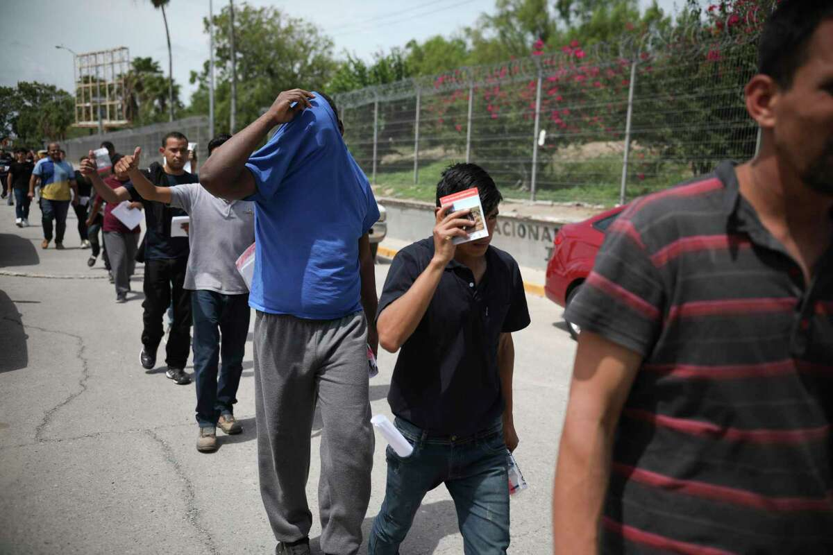 FILE - In this July 31, 2019, file photo, migrants return to Mexico, using the Puerta Mexico bridge that crosses the Rio Grande river in Matamoros, Mexico, on the border with Brownsville, Texas. A federal judge on Tuesday, Jan. 26, 2021, barred the U.S. government from enforcing a 100-day deportation moratorium that is a key immigration priority of President Joe Biden. U.S. District Judge Drew Tipton issued a temporary restraining order sought by Texas, which sued on Friday against a Department of Homeland Security memo that instructed immigration agencies to pause most deportations. Tipton said the Biden administration had failed