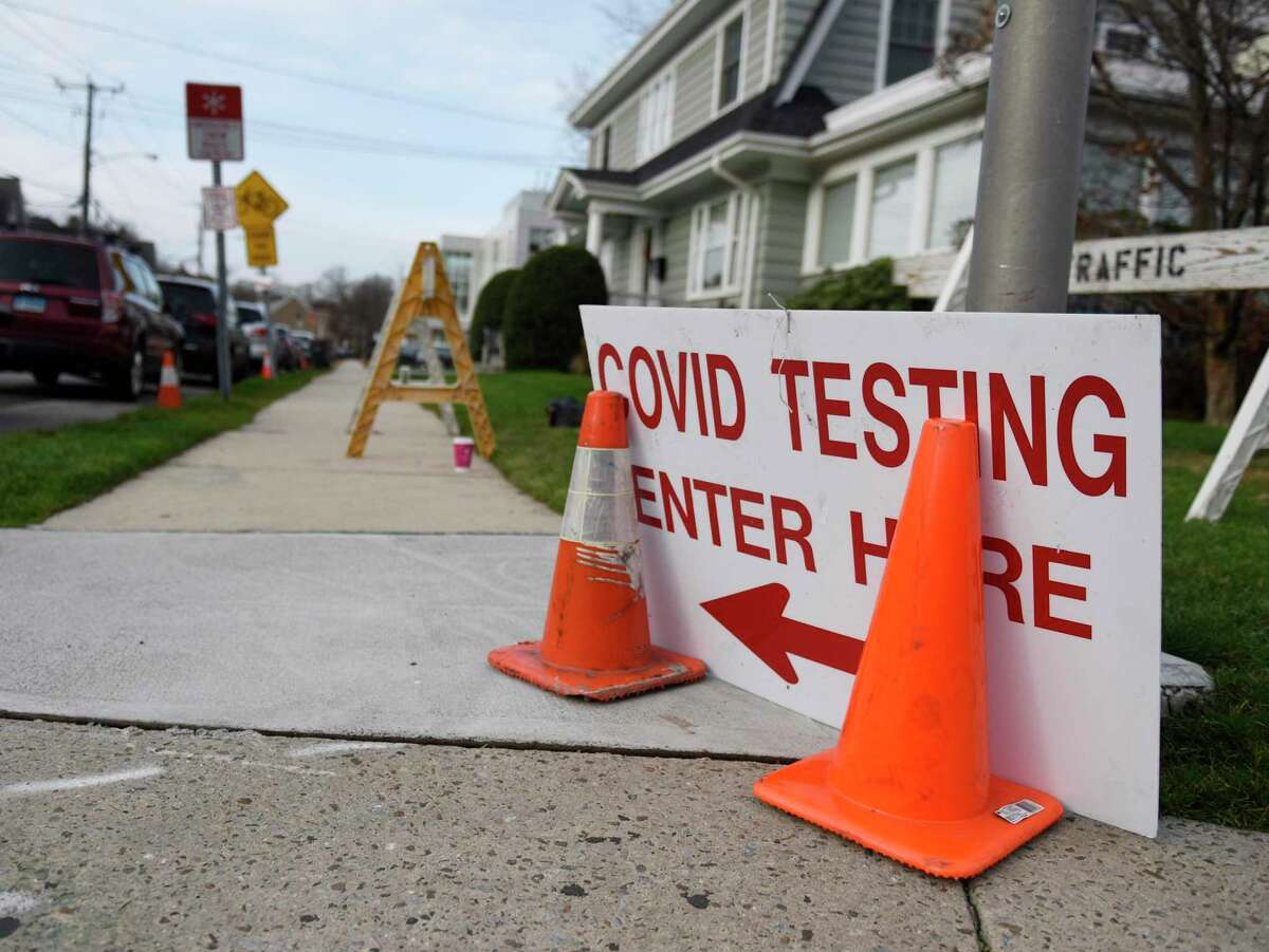 A sign directs patients to the COVID-19 testing line outside Community Health Center in Stamford, Conn. Wednesday, Dec. 2, 2020. Community Health Center's COVID-19 testing line has stretched around the block with patients often waiting several hours.
