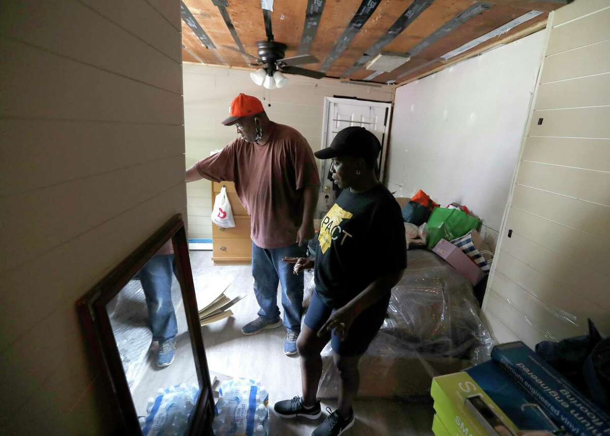 Lawrence Hester, a member of the Harvey Forgotten Survivors Caucus, Sandra Edwards' with repairs in her home, Wednesday, August 26, 2020, in Houston, which is still damaged from Hurricane Harvey, three years ago.