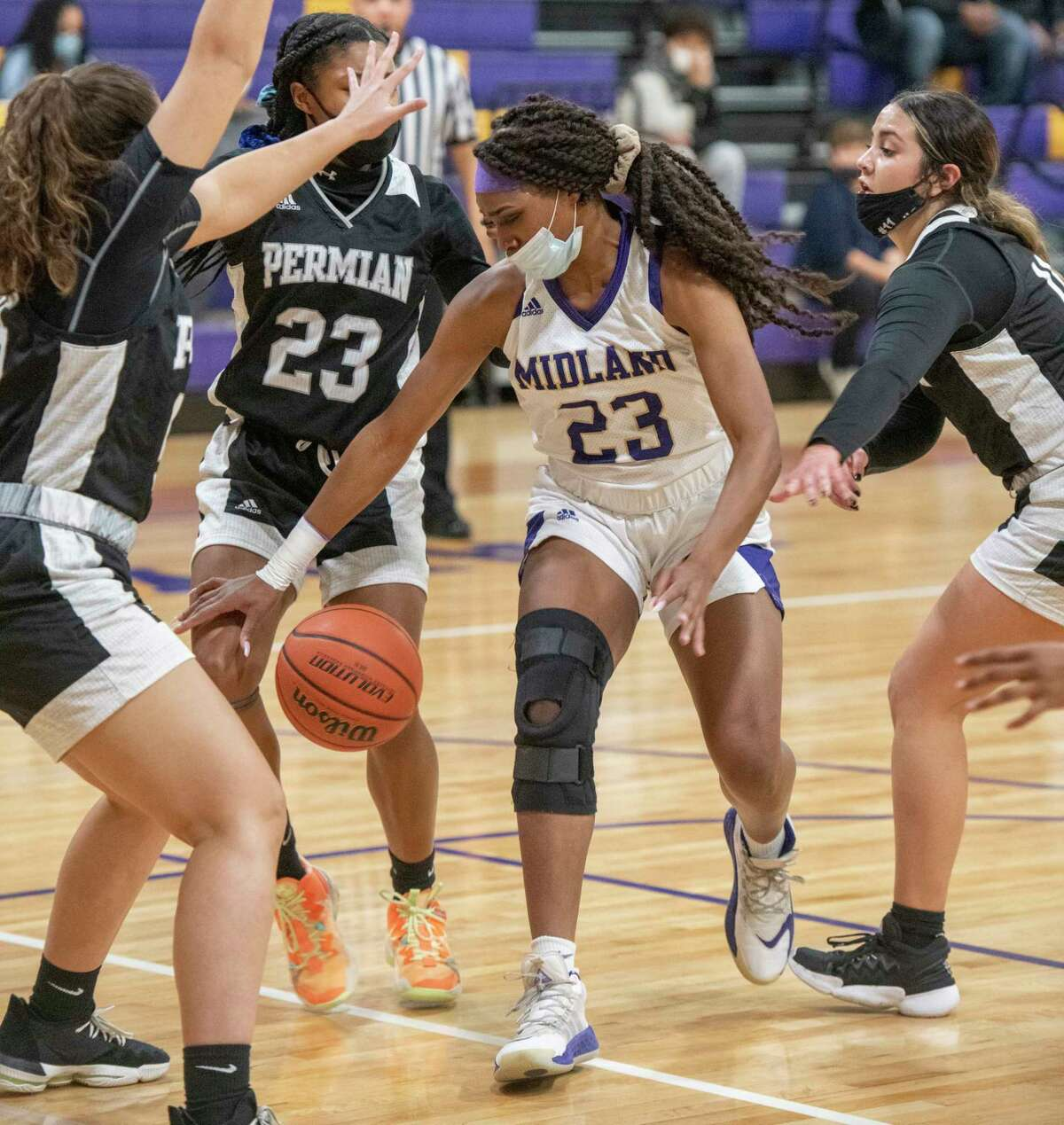 Midland Hhigh's Kobe Powell looses control as she tries to drive the lane between Permian defenders 01/26/2021 at the Midland High gym. Tim Fischer/Reporter-Telegram
