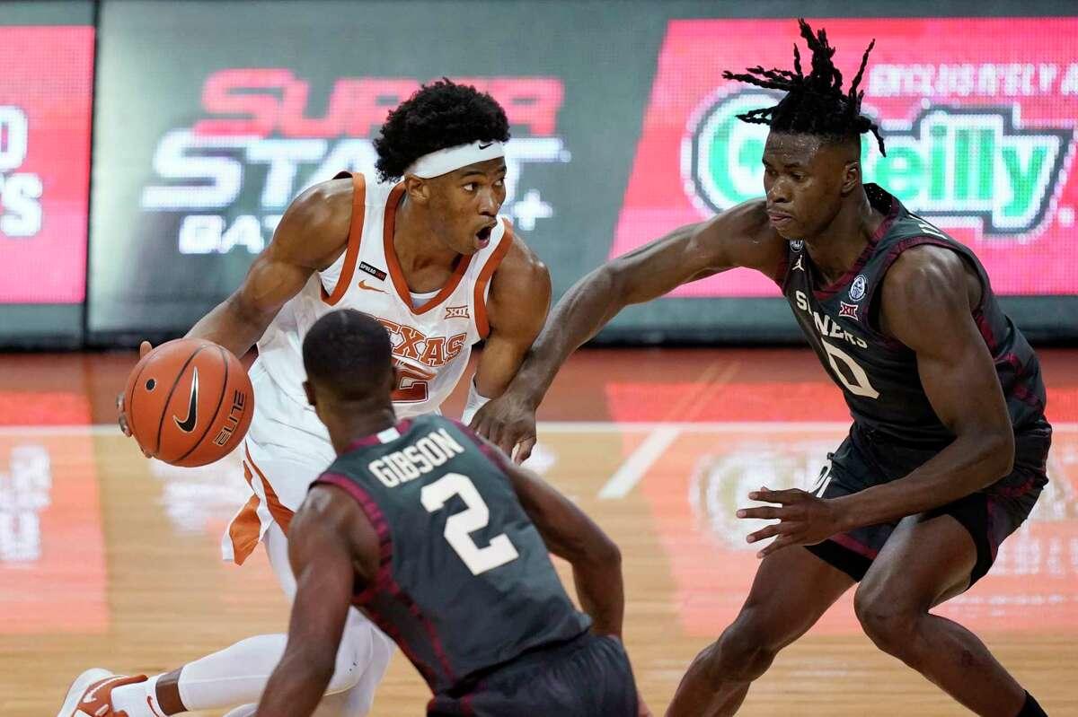 Texas forward Kai Jones (22) drives against Oklahoma guard Umoja Gibson (2) and forward Victor Iwuakor (0) during the first half of an NCAA college basketball game Tuesday, Jan. 26, 2021, in Austin, Texas. (AP Photo/Eric Gay)