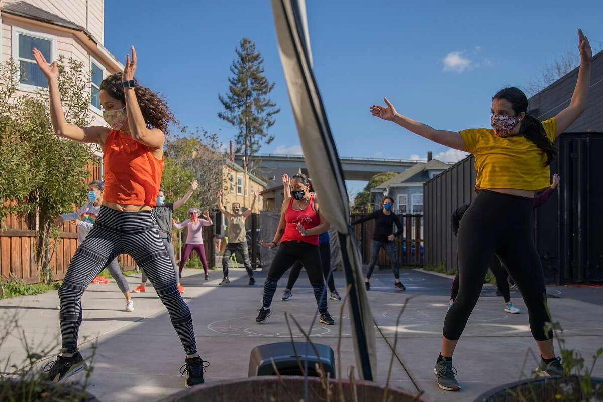 Fitness instructors Andreina Febres (left) and Adriana Oyarzun lead an outdoor Zumba class in Oakland. The pair began teaching classes virtually in early 2020 and launched their online Making Waves Studios in June. Mostly online, the instructors do an occasional in-person session outdoors, shown here. Students are masked and dance in socially distanced circles.