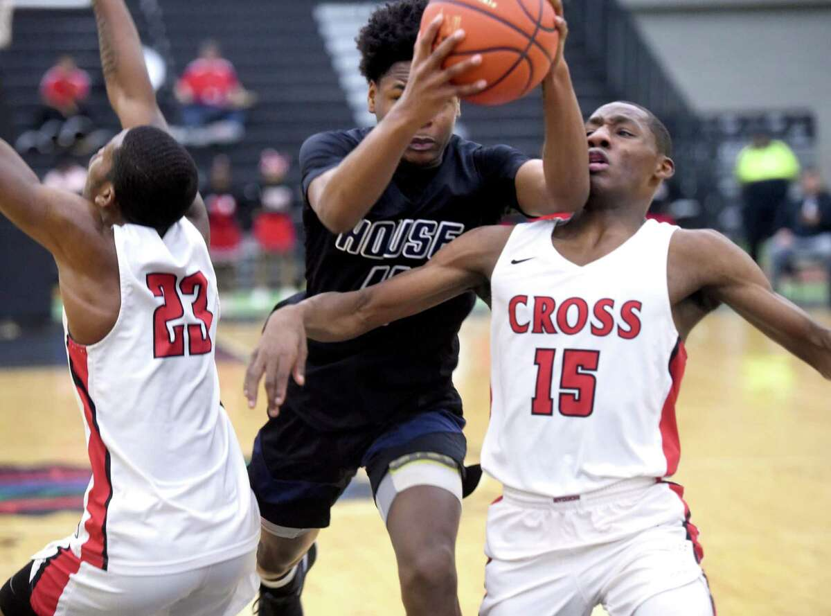 Evan Scott (center) of Hillhouse barrels his way toward the basket between Jaleem Sayles (left) and Jayvon Taylor (right) of Wilbur Cross at the Floyd Little Athletic Center in New Haven on February 20, 2020.