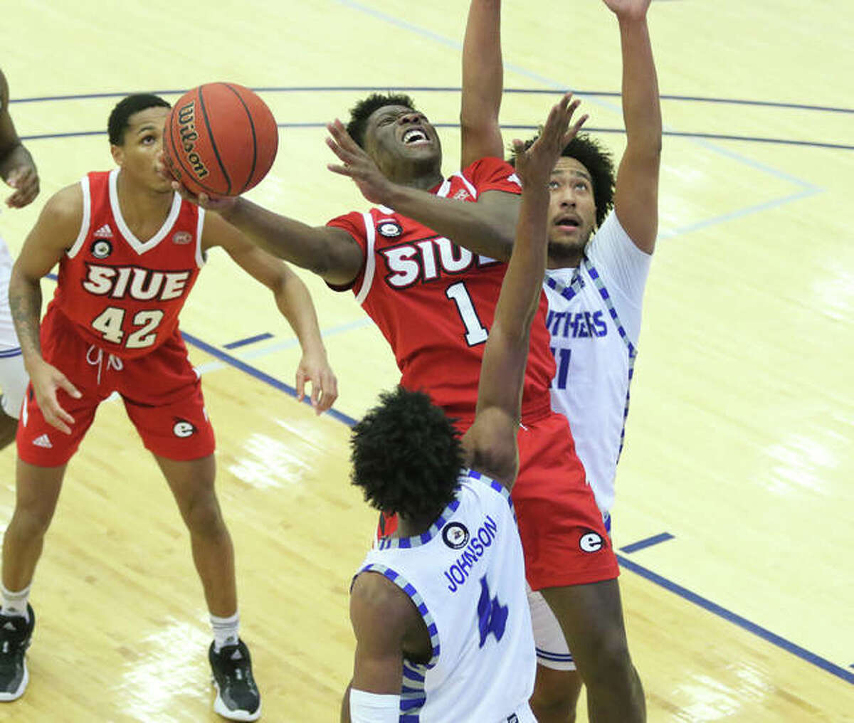 SIUE's Mike Adewunmi (1) scores between Eastern Illinoi's Barlow Alleruzzo IV (right) and Marvin Johnson (4) in an OVC men's basketball game Tuesday night at Lantz Arena in Charleston.
