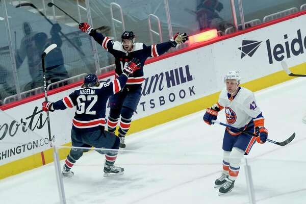 Capitals defenseman Justin Schultz, right, raises his arms to celebrate with teammate Carl Hagelin (62) after scoring the winning goal with less than 30 seconds left in the third period of Washington's game vs. the New York Islanders on Tuesday night.