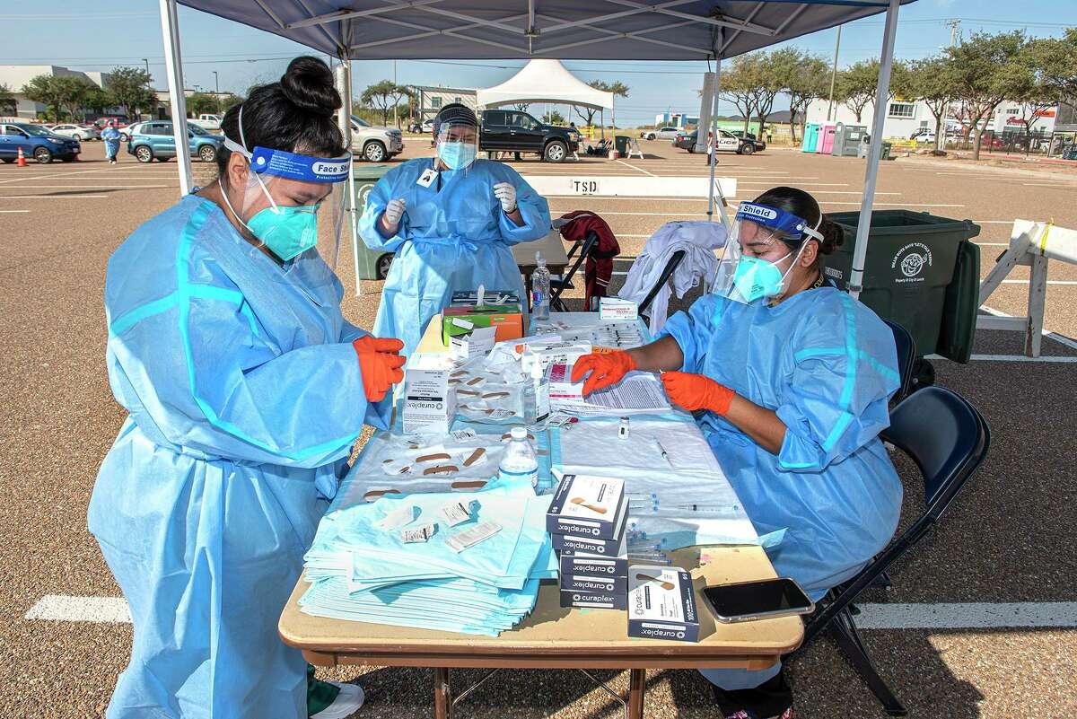 Las estudiantes de enfermería de Laredo College Viviana Alexa López, Sabrina Arias y su profesora Jeannette Johnson ayudan a preparar y distribuir la segunda vacuna contra COVID-19, el martes 26 de enero de 2021 en el Sames Auto Arena, a los laredenses que recibieron la primera vacuna durante el drive-thru de la vacuna TAMIU a principios de este mes.