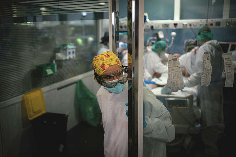A hospital worker looks out from an intensive care unit as a COVID-19 patient receives treatment. Photo: Felipe Dana   AP