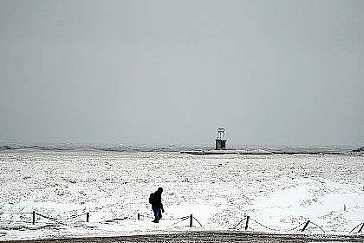 A lone man walks Tuesday along a frozen section of the North Avenue beach on Lake Michigan north of downtown Chicago. A major winter storm dumped more than a foot of snow on parts of the Midwest from central Kansas northeast to Chicago and southern Michigan.