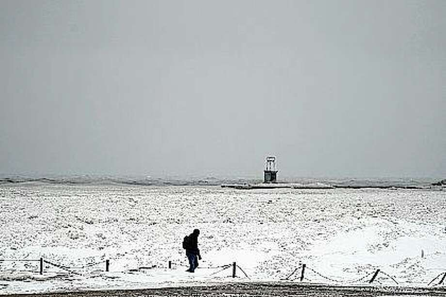 A lone man walks Tuesday along a frozen section of the North Avenue beach on Lake Michigan north of downtown Chicago. A major winter storm dumped more than a foot of snow on parts of the Midwest from central Kansas northeast to Chicago and southern Michigan. Photo: Charles Rex Arbogast | Associated Press