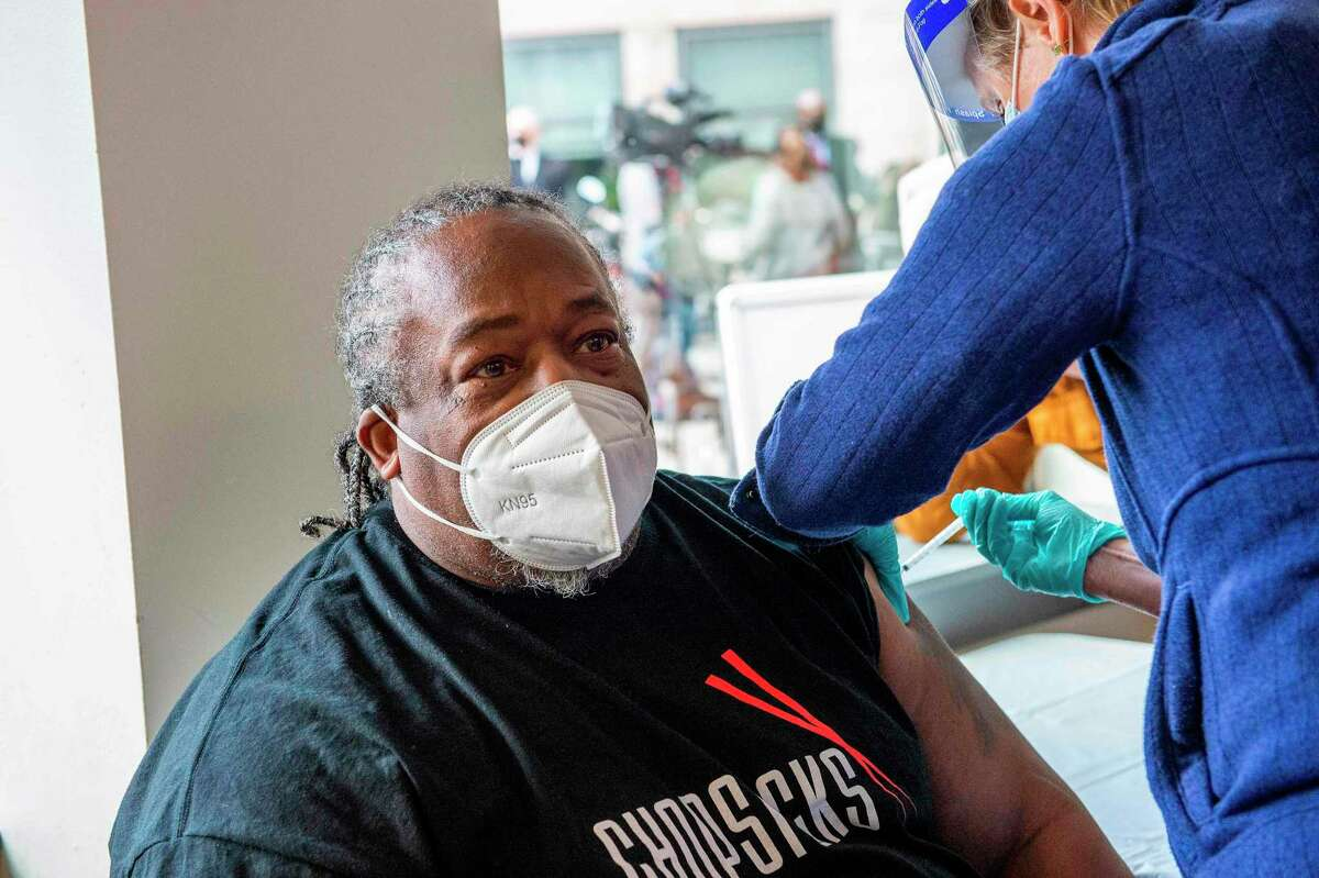 Frank Tate, a staff member and former client of The Open Hearth men's shelter, receives the Pfizer-BioNTech Covid-19 vaccine from a Mobile Vaccination Clinic run by Hartford HealthCare in Hartford, Connecticut on January 22, 2021.