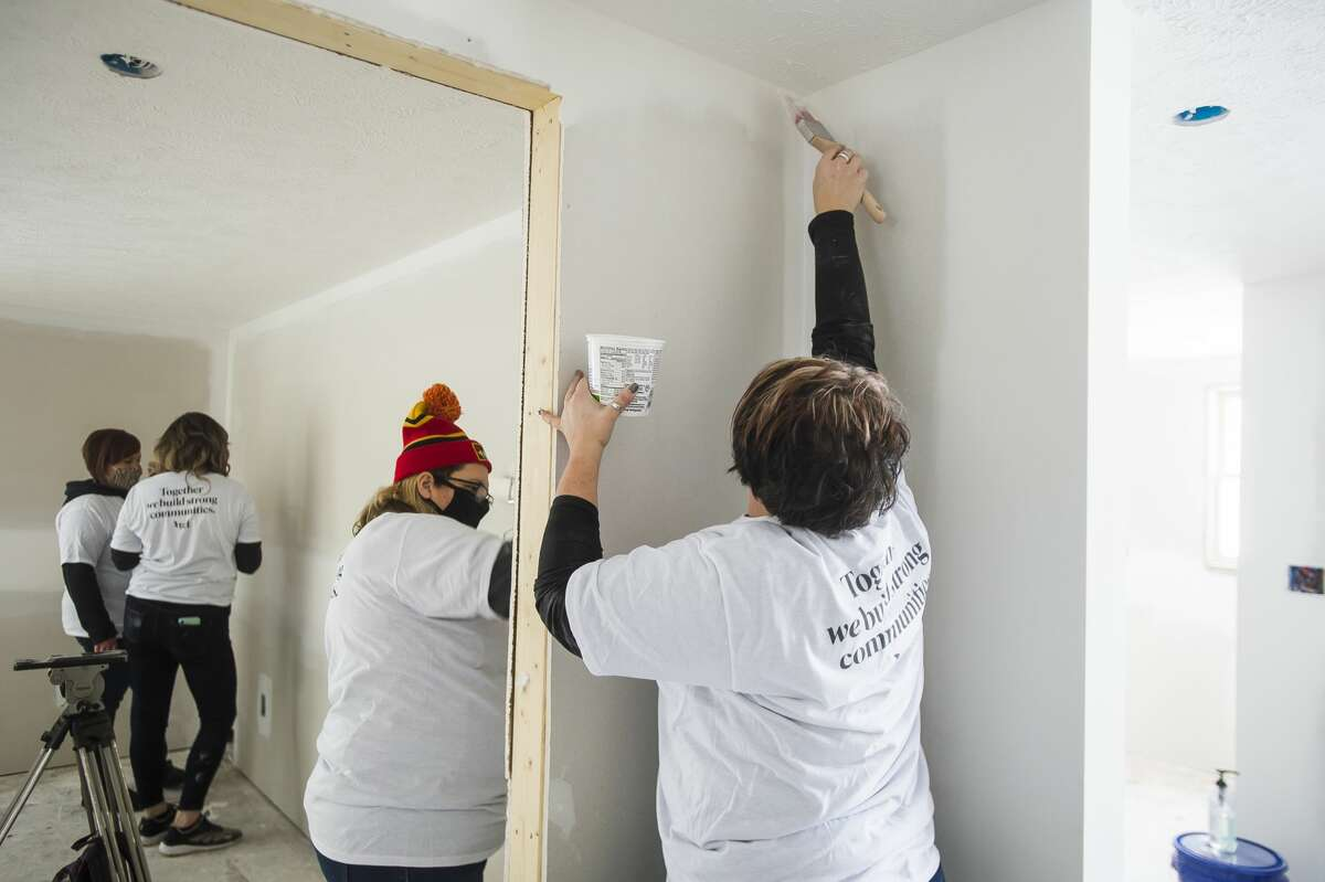Volunteers from TCF Bank apply primer to walls as work continues on a home for the reBuild Together project through a partnership between Midland County Habitat for Humanity and United Way of Midland County Wednesday, Jan. 27, 2021 in Midland. (Katy Kildee/kkildee@mdn.net)