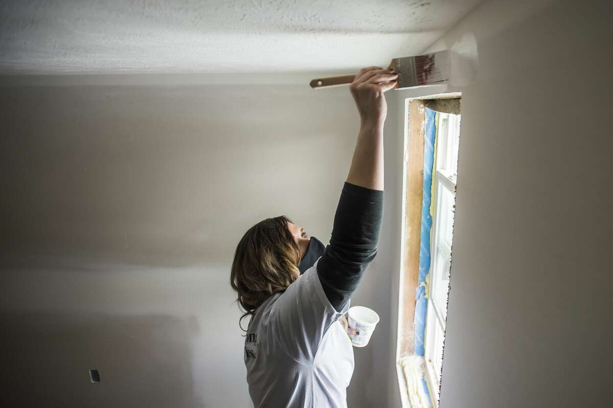 Katie Abbate, a volunteer from TCF Bank, applies primer to a wall as work continues on a home for the reBuild Together project through a partnership between Midland County Habitat for Humanity and United Way of Midland County Wednesday, Jan. 27, 2021 in Midland. (Katy Kildee/kkildee@mdn.net)