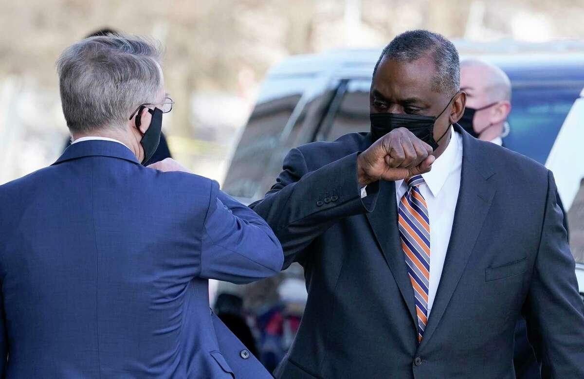 Lloyd Austin, President Biden's nominee as Secretary of Defense, right, greets Deputy Secretary on Jan. 22, 2021, in arriving at the Pentagon in Arlington, Va. (AP Photo/Alex Brandon)