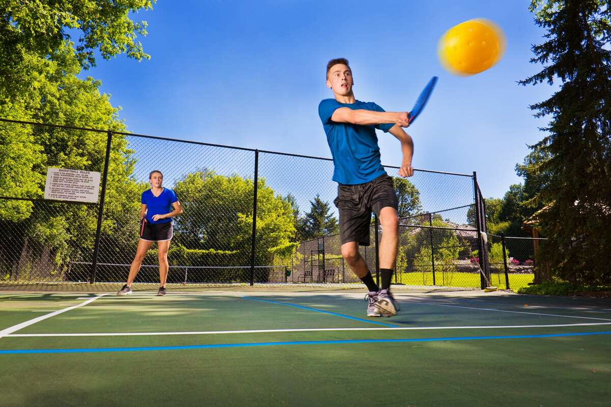 A file photo of a young teen boy and girl playing doubles pickle ball in a court.