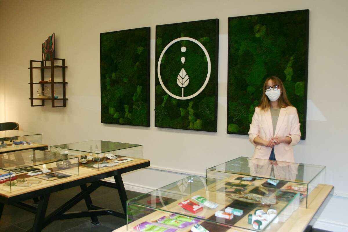 Chyna Blu, general manager of The Wellflower, a new medical marijuana dispensary in downtown Big Rapids, assists customers in determining what products will best suit their needs.