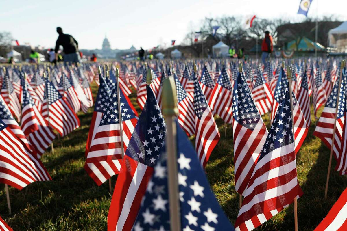 Workers begin to remove a display of flags on the National Mall one day after the inauguration of President Joe Biden in Washington. As one of his first acts, Biden offered a sweeping immigration overhaul that would provide a path to U.S. citizenship for the estimated 11 million people who are in the United States illegally. It would also codify provisions wiping out some of President Donald Trump's signature hard-line policies, including trying to end existing, protected legal status for many immigrants brought to the U.S. as children and crackdowns on asylum rules.