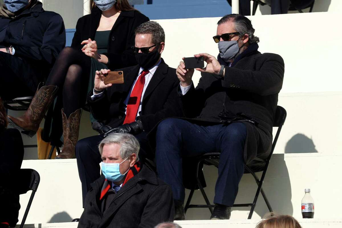 Senator Ted Cruz, a Republican from Texas, takes photographs with a mobile device during the 59th presidential inauguration in Washington, D.C., U.S., on Wednesday, Jan. 20, 2021. Biden will propose a broad immigration overhaul on his first day as president, including a shortened pathway to U.S. citizenship for undocumented migrants - a complete reversal from Donald Trump's immigration restrictions and crackdowns, but one that faces major roadblocks in Congress.