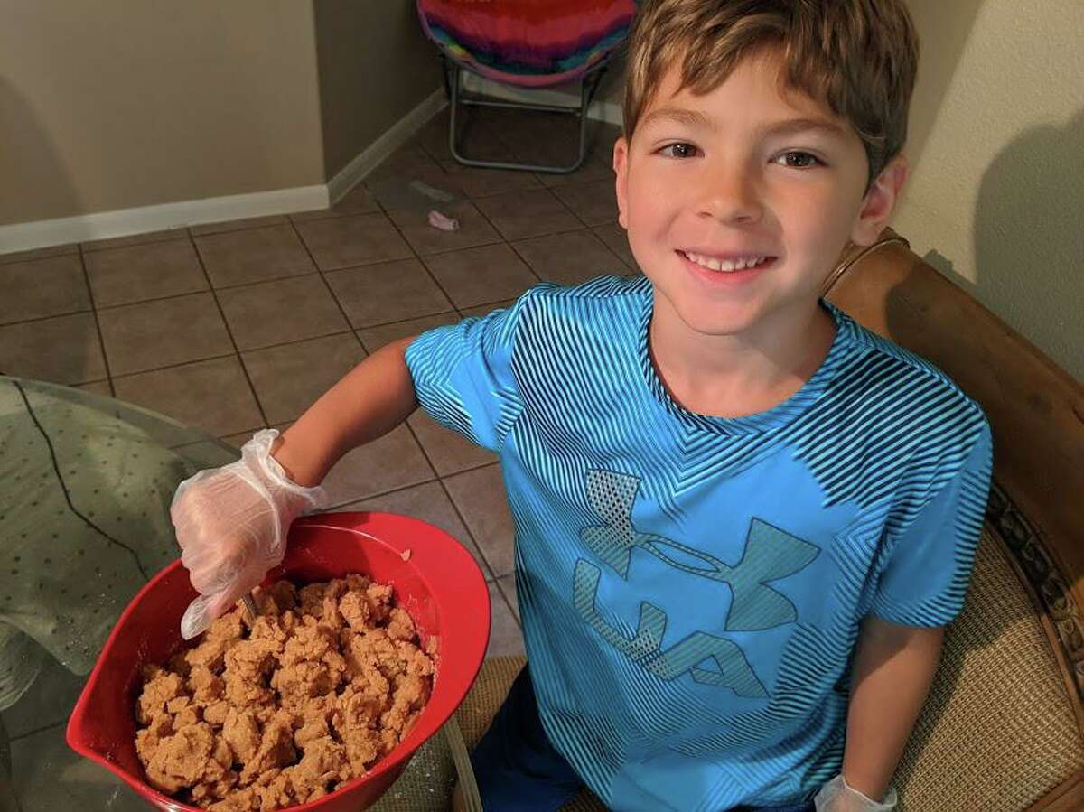 Isaiah Hodge, 7, poses while mixing his Puppy Dough dog treats. He started the business in July to buy an electric unicycle and has since sold around $1,000 worth.