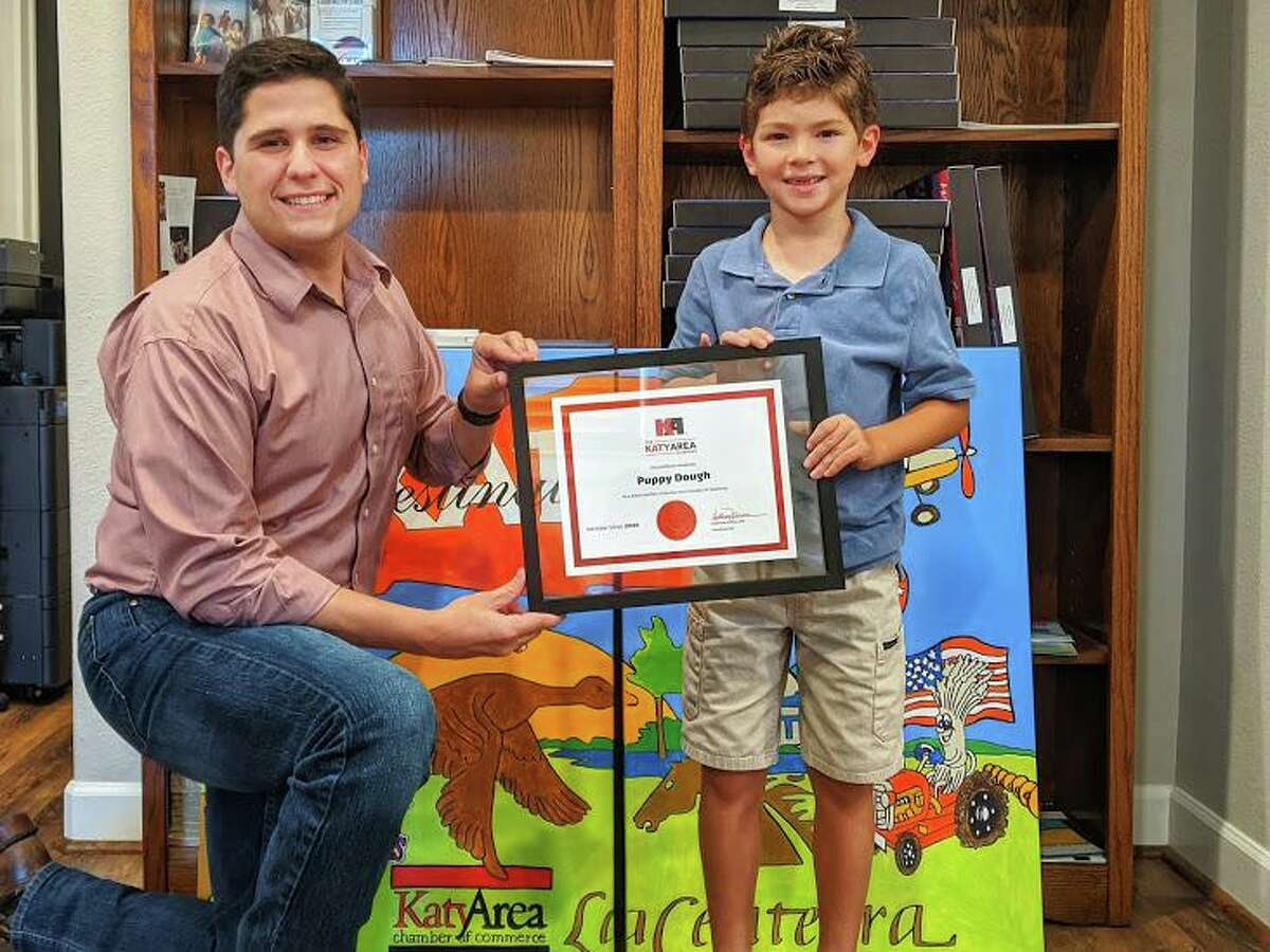Matthew Ferraro, Katy Area Chamber of Commerce president and CEO, poses with Puppy Dough Owner Isaiah Hodge, 7, the chamber's youngest member.