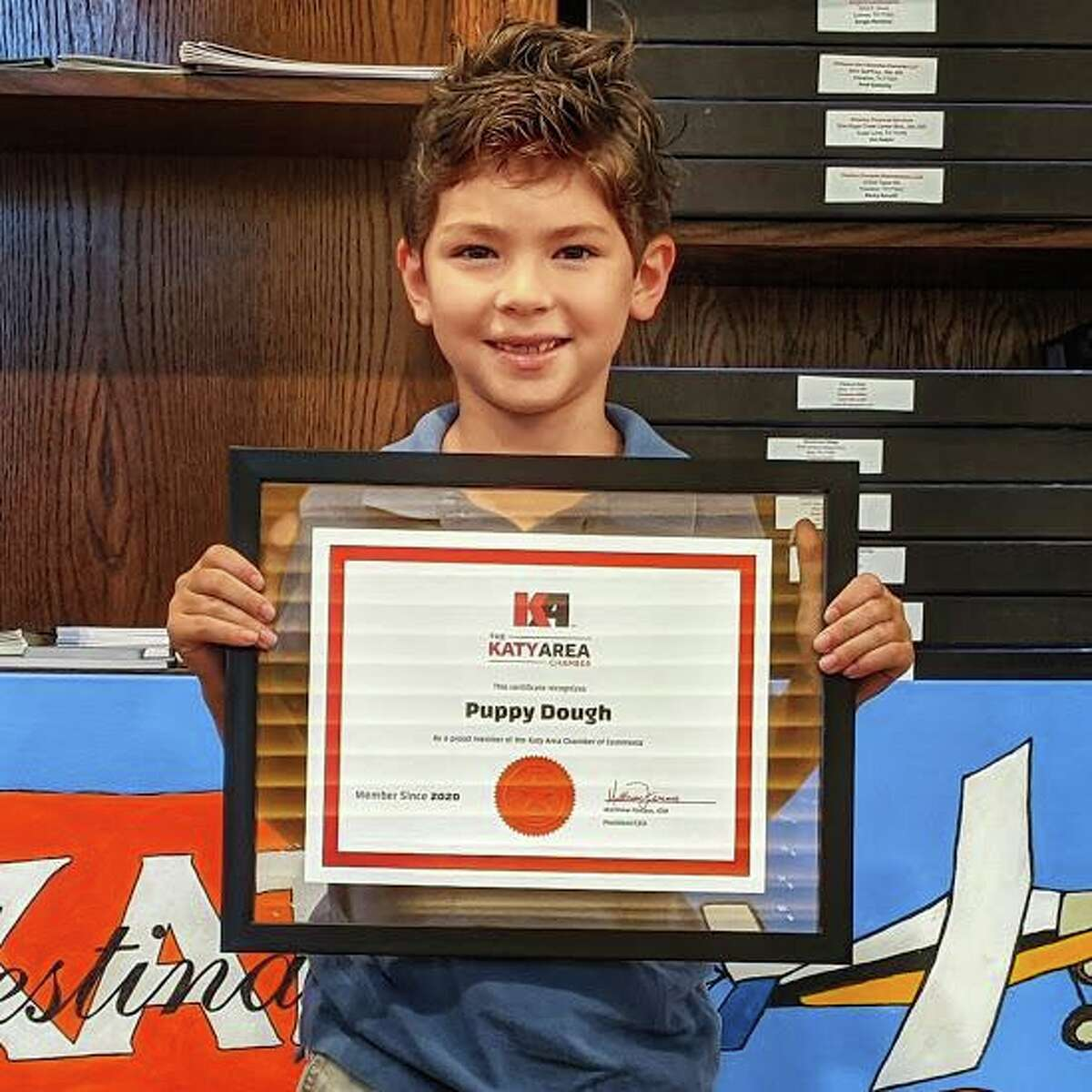 Puppy Dough Owner Isaiah Hodge, 7, shows his plaque as a member of the Katy Area Chamber of Commerce.