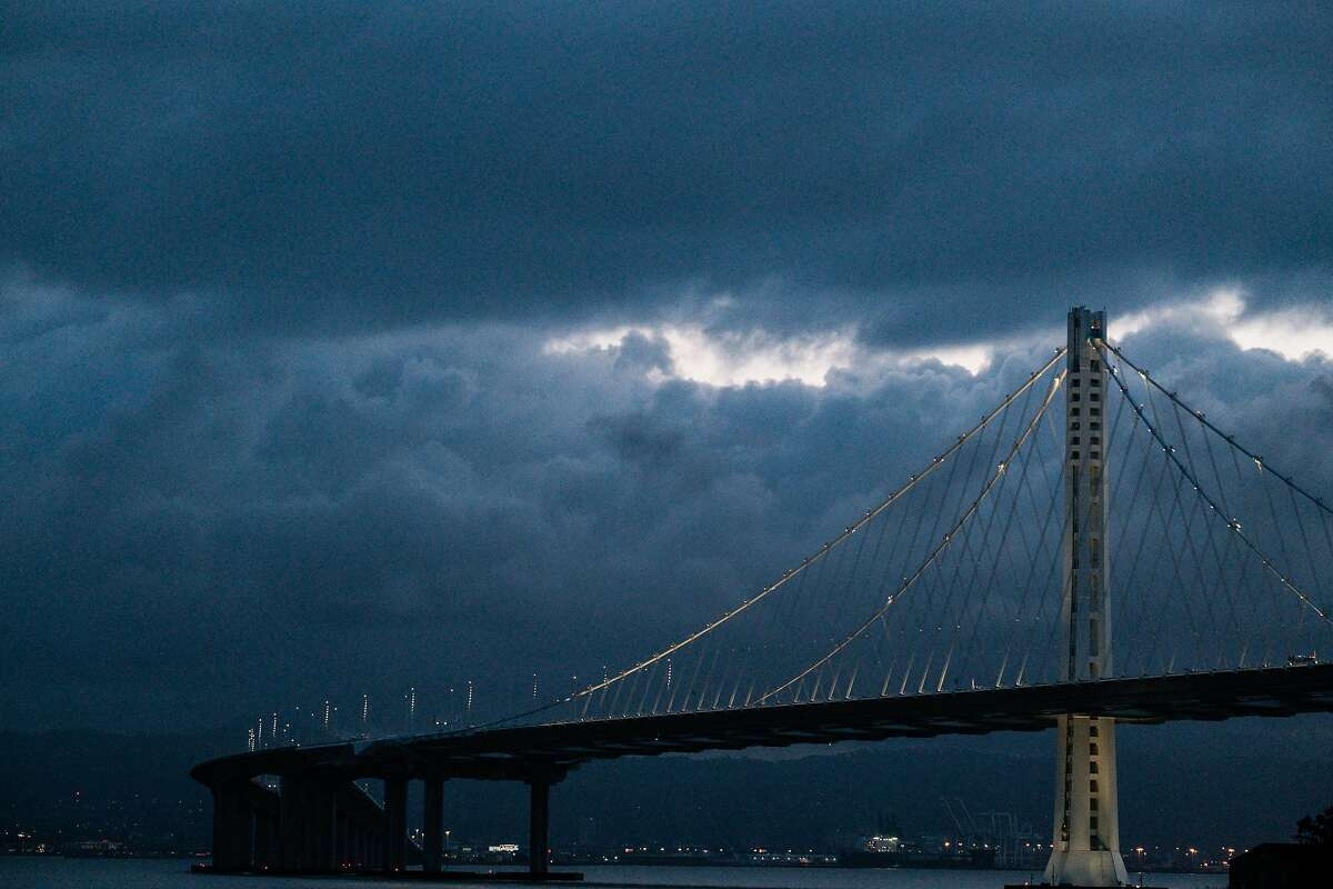 A file photo of the Bay Bridge is seen with large clouds looming over the East Bay as seen form Treasure Island in San Francisco. Aburst of rain is expected to drench the Bay Area this weekend, bringing much-needed moisture to a parched region.