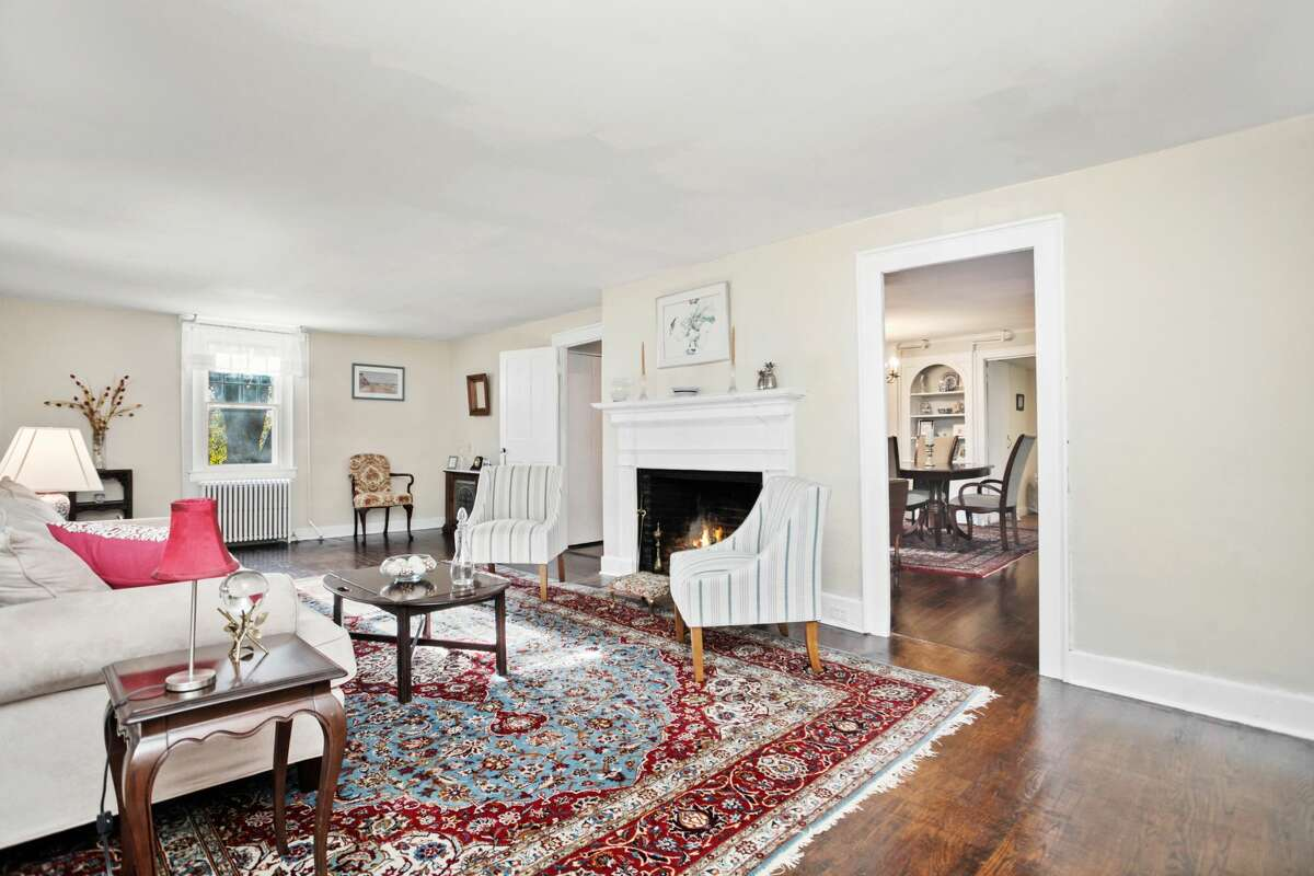 """Living room at 420 Tashua Road, Trumbull. The house is well-preserved. It comprises four bedrooms, 2.5 baths, four fireplaces - some with beehive ovens -exposed beams in some rooms, """"queen's mast"""" original flooring, arched doorways, handmade interior doors, a wet bar area and many newer Pella windows. In the attic there is a smokehouse, and in the basement, a circular hand-made brick root cellar that could be converted into a wine cellar. """"Originally part of a large farm, this home consists of three sections, all of which predate 1800,"""" Fowler said. """"The main house and the other two sections were flawlessly moved from other locations, and the entire home has been updated over time to blend old world charm with today's modern amenities."""""""