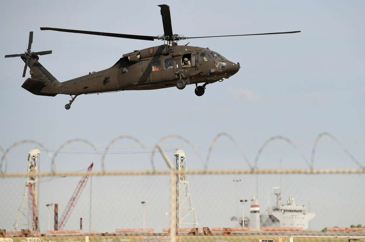 Military helicopters descend for a landing at the Port of Beaumont Wednesday morning. The aircraft are part 1,500 military cargo being staged at the port as part of the U.S. Army 842nd Transportation Battalion's operation to deploy the equipment to Europe for 1st Combat Aviation Brigade's training exercises with NATO allies. The U.S. Army's