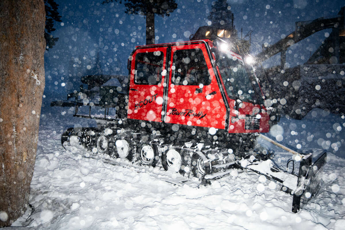 Workers use a snowplow during heavy snowfall overnight on Jan. 27, 2021.