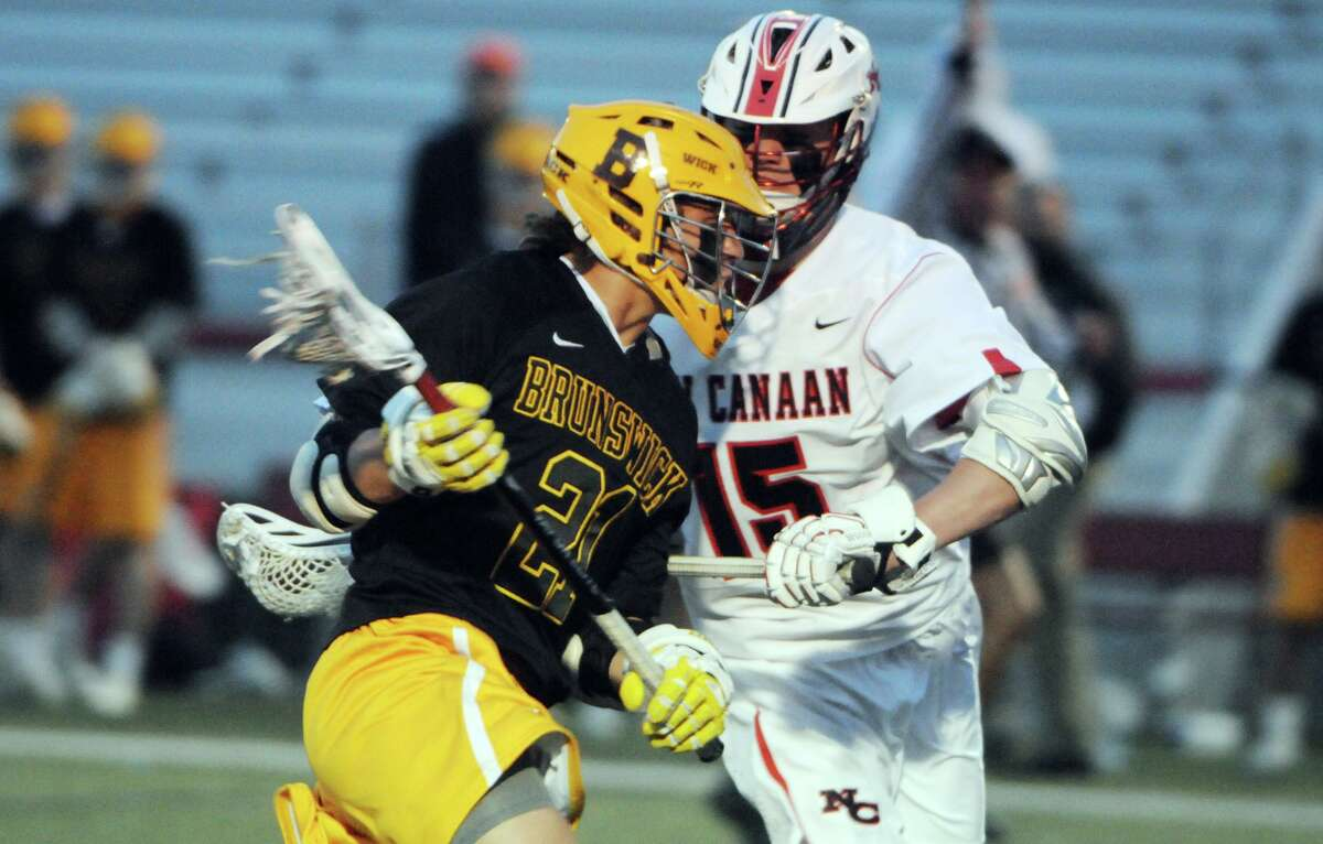 Brunswick's John Fox, a New Canaan resident, collides with the Rams' Max Begoon during a boys lacrosse gamein 2015.