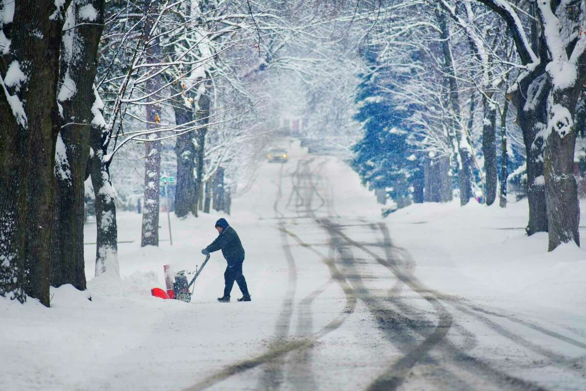 A man uses a snowblower to clear snow off a driveway on Wednesday, Jan. 27, 2021, in East Greenbush, N.Y. (Paul Buckowski/Times Union)