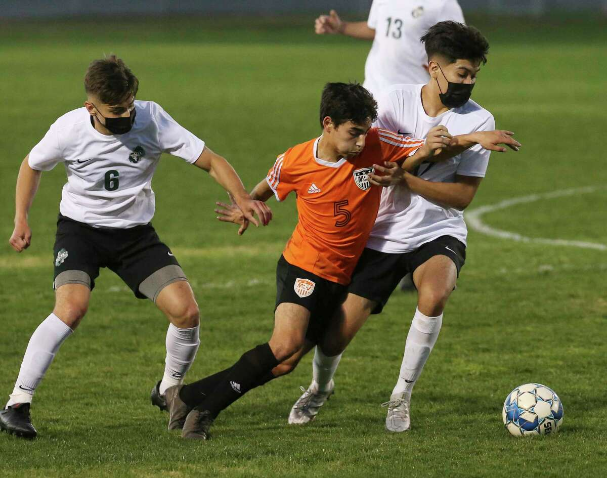 Medina Valley's Vicente Gonzales (05) battles Johan Melendez (06) and Aaron Rivera (17) of Southwest in boys high school soccer on Tuesday, Jan 26, 2021. Southwest was defending a 28-game win streak as they took down Medina Valley, 8-0.