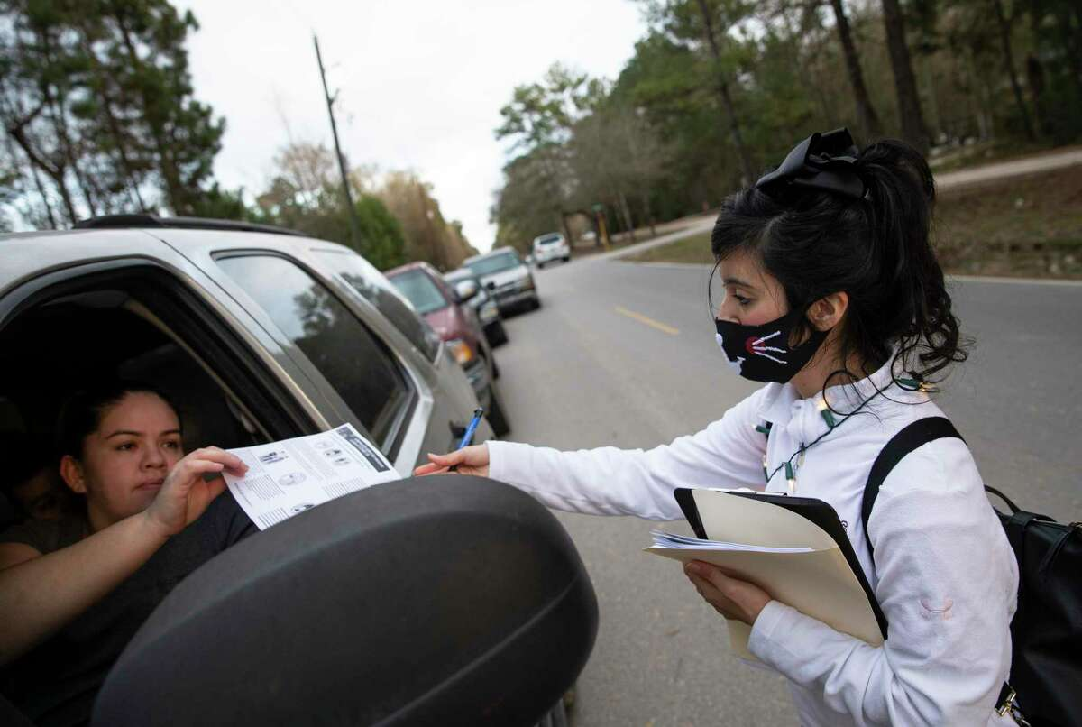 Volunteer Adilene Ramirez hands out fliers with information about COVID-19 and the vaccine to people who show up for a weekly food distribution Monday, Jan. 18, 2021, in New Caney. Texas Familias Council put in efforts to encourage Latinos, many of whom showed up for the food distribution, to get vaccinated and distribute accurate information about the pandemic amid some skepticism and misinformation about the coronavirus.
