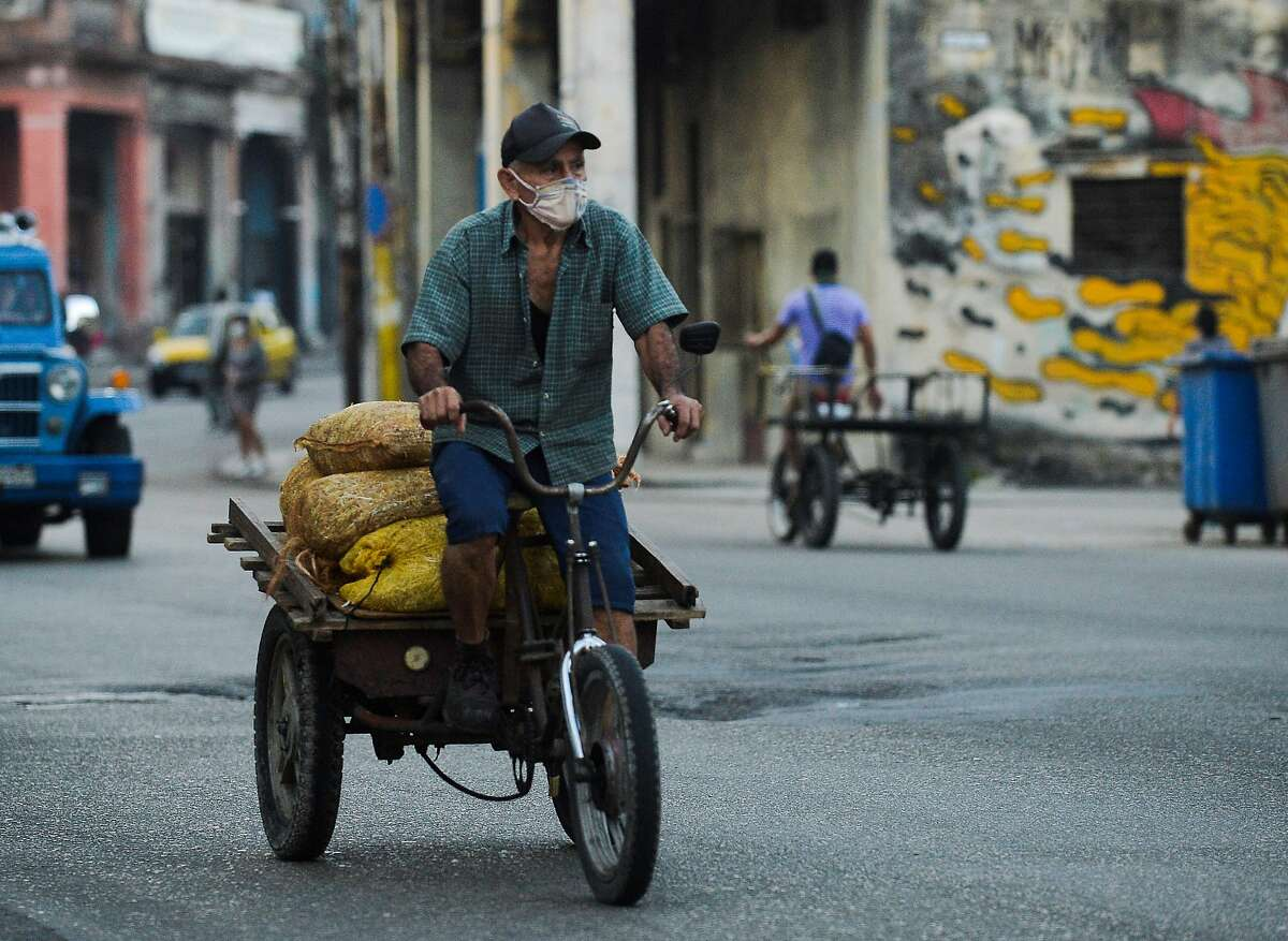 A man transports bags with vegetables for sale in Havana on Jan. 21.