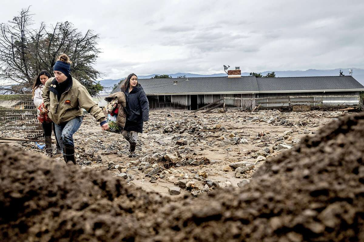 Hana Mohsin, right, carries belongings from a neighbor's home which was damaged in a mudslide on Wednesday, Jan. 27, 2021, in Salinas, Calif. The area, located beneath the River Fire burn scar, is susceptible to landslides as heavy rains hit hillsides scorched during last year's wildfires. (AP Photo/Noah Berger)