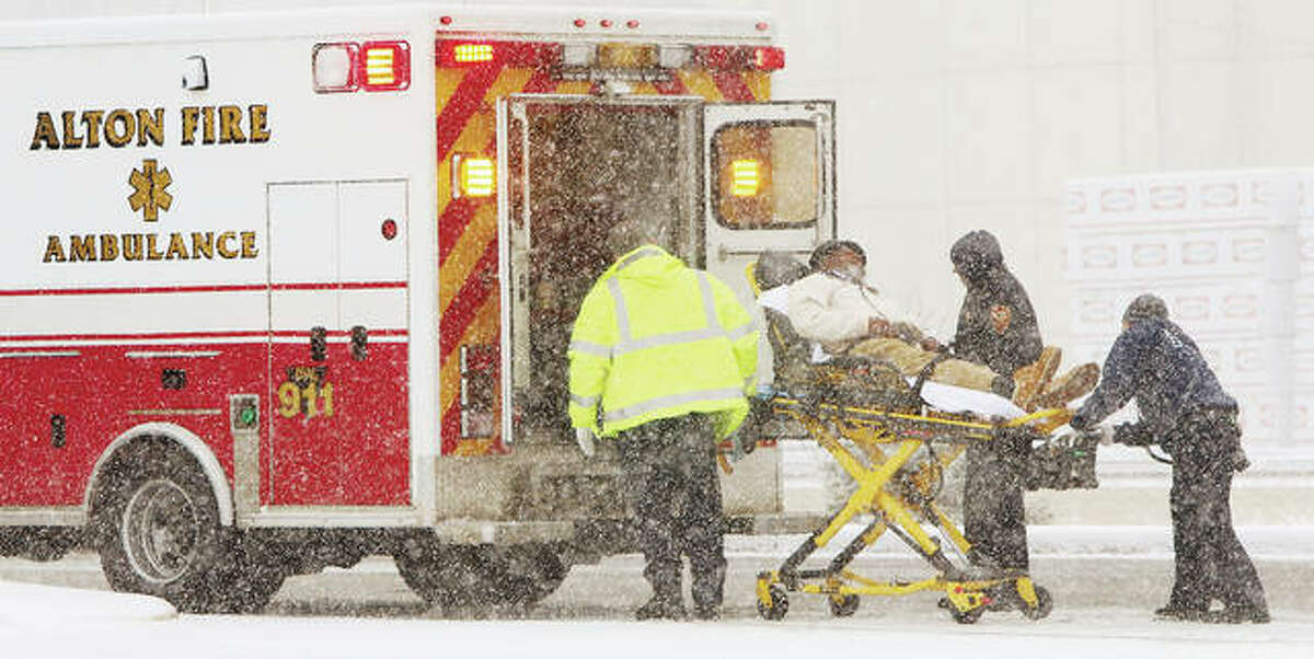 At Martin Luther King Boulevard and Ridge Street in Alton, fire department paramedics worked in what looked like blizzard conditions as they loaded a patient for transport following a crash between a GMC pickup truck and a Toyota Prius.