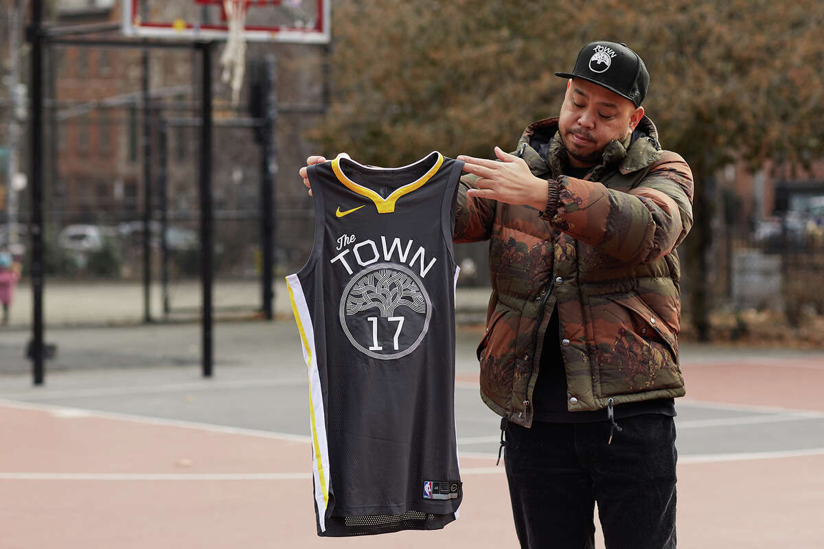 Designer and artist Dustin Canalin holding a Golden State Warriors' The Town jersey.