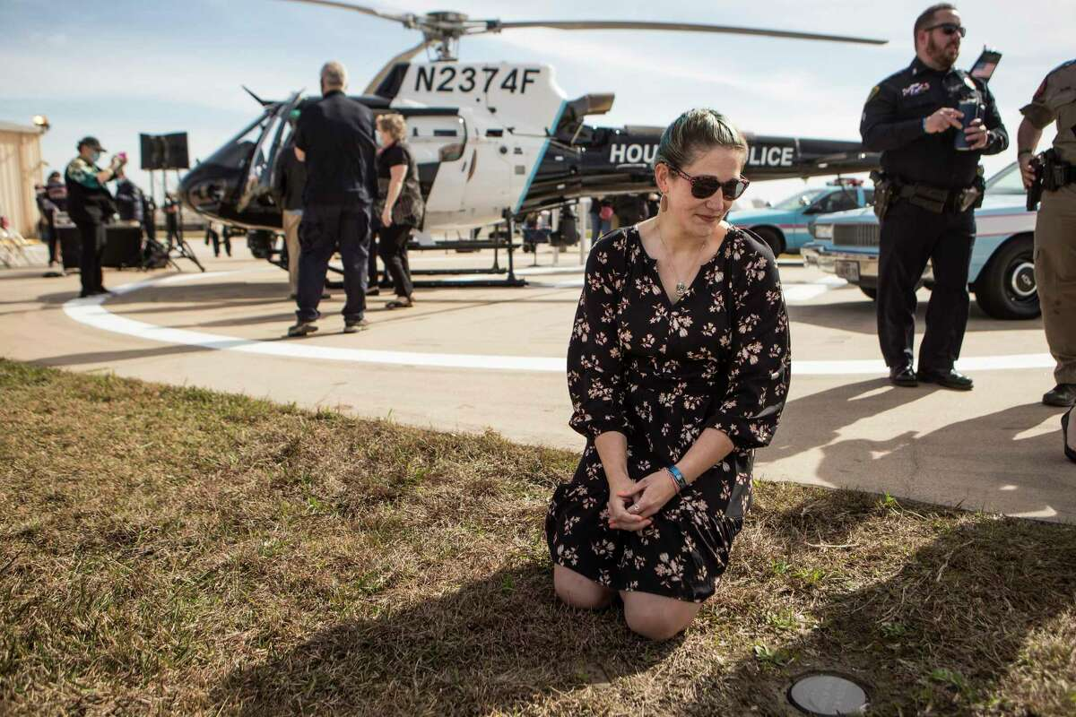 Keira Knox kneels next to the spot on the airfield where some of the ashes of her husband, fallen Police Officer/Tactical Flight Officer Jason Knox, are buried Wednesday, Jan. 27, 2021 in Houston. Knox was honored by HPD as they dedicated the department's newest helicopter in his name. The H125 Airbus incorporates Officer Knox's badge number of 2374 into its registration number, which is N2374F. The fuselage also features a vintage HPD blue stripe as a nod to Knox's passion for the department's history. Knox was killed in the line of duty on May 2, 2020, when the HPD helicopter he was in crashed while on a call-for-service.