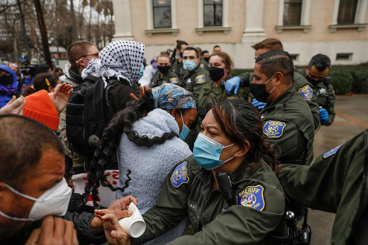 Sheriffs get in a skirmish as they push demonstrators to the sidewalk during a protest outside the Santa Clara County Courthouse in San Jose where protesters attempted to halt eviction proceedings from taking place on Wednesday, Jan. 27, 2021 in San Jose, California.