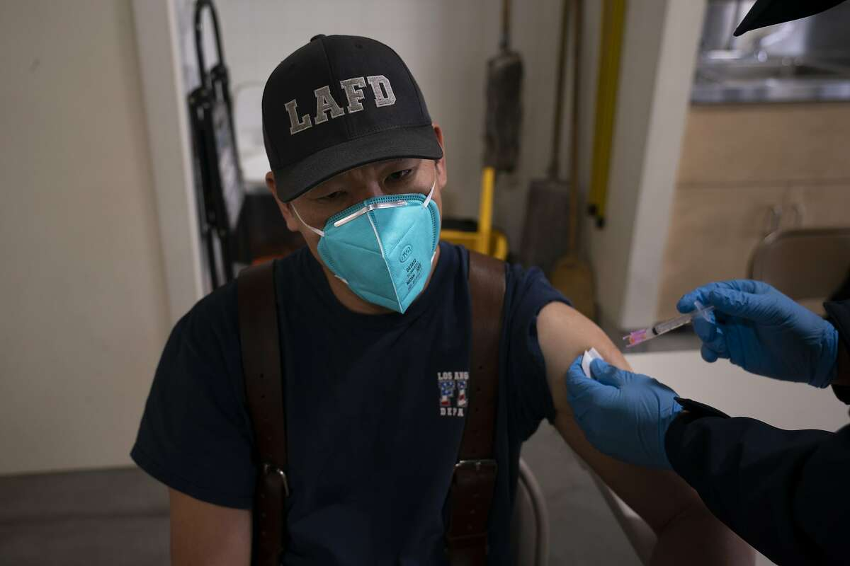 Firefighter Henry Hsieh receives his second dose of the coronavirus vaccine at a fire station in Los Angeles in January. Most Californians want to get the vaccine.