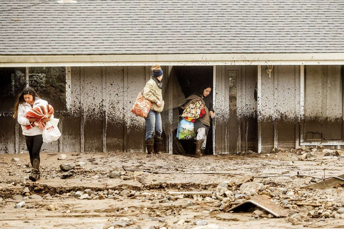 Hana Mohsin, right, carries belongings from a neighbor's home that was damaged in a mudslide on Wednesday, Jan. 27, 2021, in Salinas, Calif. The area, located beneath the River Fire burn scar, is susceptible to landslides as heavy rains hit hillsides scorched during last year's wildfires.