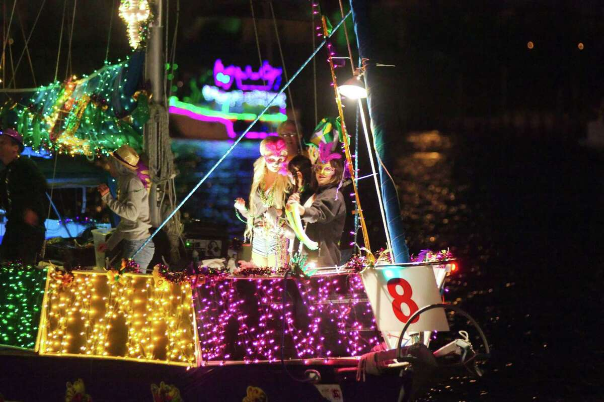Costumed passengers wave from the deck of a Mardi Gras-themed decorated boat as they pass the Kemah Boardwalk in a previous Yachty Gras parade.