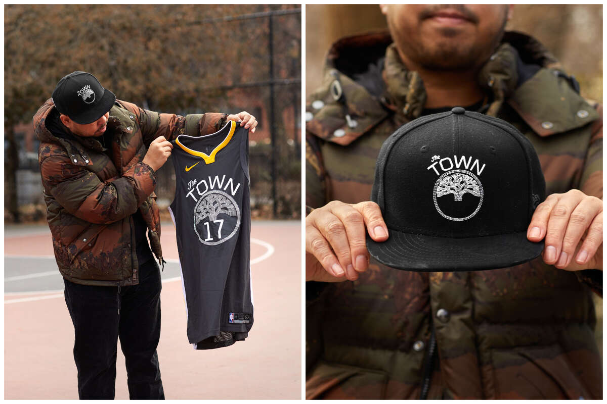 Designer and artist Dustin Canalin holding a Golden State Warriors' The Town jersey and hat.
