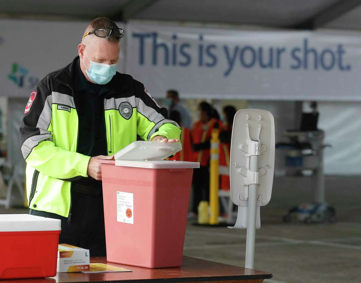 Rex Morris, a paramedic with the Montgomery County Hospital District, prepares his station at Montgomery County's second mass COVID-19 vaccination site at CHI St. Luke's Health - The Woodlands Hospital, Tuesday, Jan. 26, 2021, in The Woodlands.